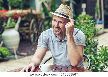 Young Attractive Guy In Sun Hat Sits In Cafe Outdoors, Drinks Coffee During Lunch Time, Rests, Enjoy