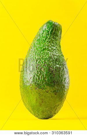 Organic Avocado On Yellow Background. Face View.