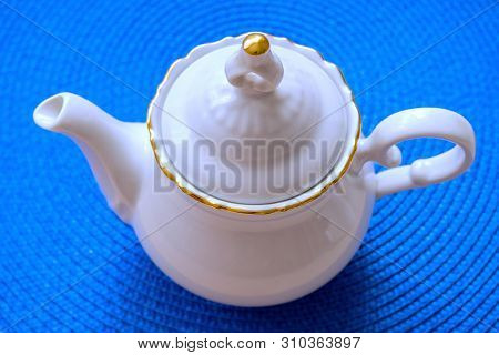 White Teapot On A Background Of Blue Wicker Mat, Soft Selective Focus
