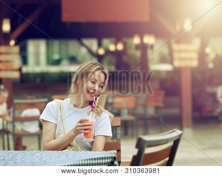 Positive Beautiful Young Female Model Feels Relaxed While Sits In Cafe, Enjoys Fresh Strawberry Smoo