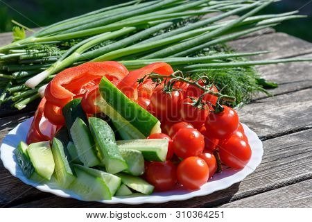 Fresh Vegetables And Greenery On A Wooden Background Outdoors.