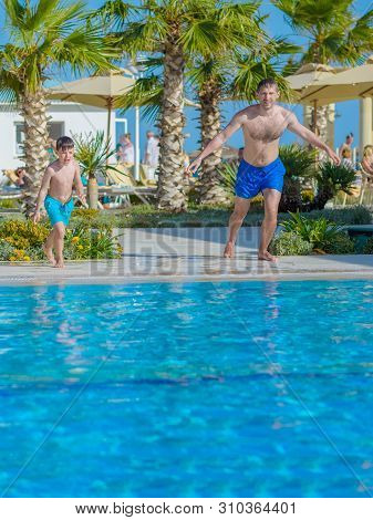 Smiling Caucasian Man And His Son Are Jumping In To The Swimming Pool At Resort On Family Vacation.