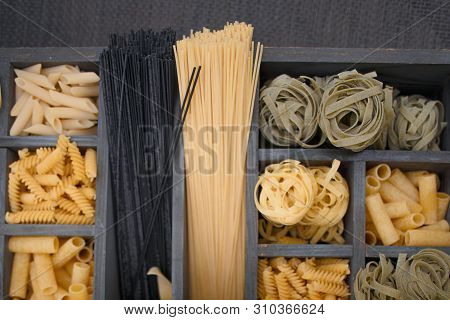 Top View Various Types Of Italian Pasta In A Wooden Box With Different Cells.