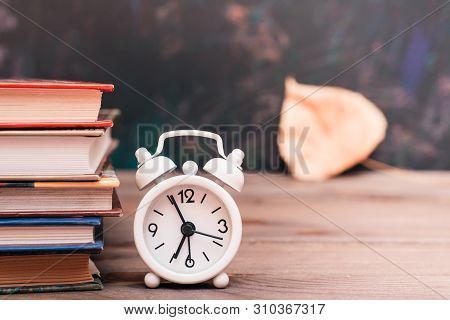 Back To School Background With Books, Clock And Fallen Leaf Over Blackboard