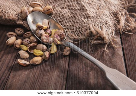 Pistachio Nuts On An Old Spoon And Composition From Old Wood And Material