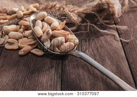 Roasted Peanuts On An Old Spoon And Composition From Old Wood And Material.