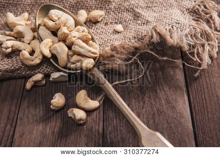 Cashew Nuts On An Old Spoon And Composition From Old Wood And Material