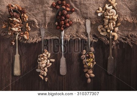 Different Types Of Nuts On Old Spoons And Compositions Made Of Old Wood And Material