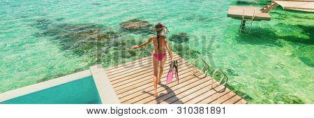 Luxury Bora Bora resort woman going snorkeling from overwater bungalow panoramic. Tahiti paradise destination vacation.