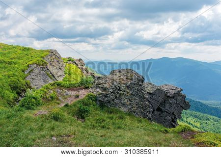 Rock On The Edge Of A Hill. Beautiful Summer Scenery In Mountains. Grass On The Slope Beneath A Clou