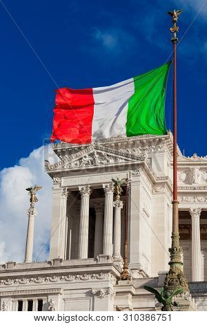 ROME, ITALY – MAY 19: Nationalism and sovereignty in Italy. 'Tricolore' Italian national flag fluttering in the wind before Altar of Nation monument, symbol of fatherland May 19, 2019 in Rome, Italy