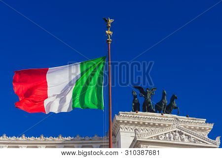 ROME, ITALY – JUNE 1: Nationalism and sovereignty in Italy. 'Tricolore' Italian national flag fluttering in the wind before Altar of Nation monument, symbol of fatherland June 1, 2016 in Rome, Italy