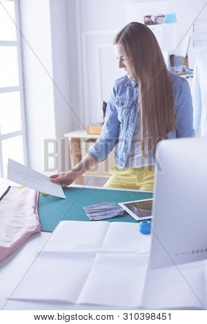 Woman American fashion designer working in atelier.