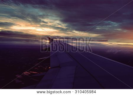 Wing Of Airplane Flying Above The Dark Rain Clouds At Sunset In Bangkok