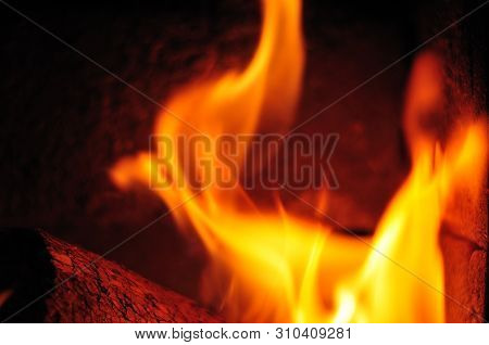 Wooden Briquet Burning In Fireplace With Chamotte Stones