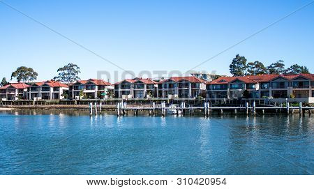 Large Waterside Houses In Suburban Community Set On Riverfront With Wooden Wharf And Boat In Foregro