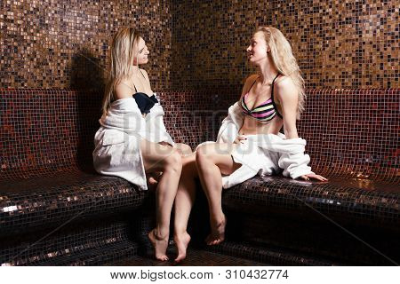 Turkish Bath Hamam. Two Cute Girls Relaxing And Talking In The Steam Room In Bath Robes. Healthy Lif