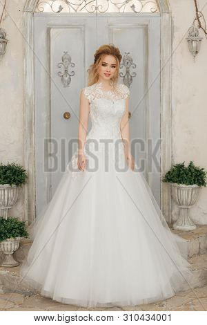 Beautiful Bride In A White Fluffy Dress, Wedding Theme, Freedom. Full-lenght Portrait On Rustic Wall