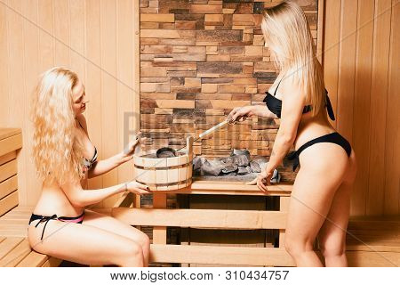Finnish Sauna. Two Blonde Girls In Bathing Suits Bathe In The Bath. Healthy Lifestyle Concept. Body