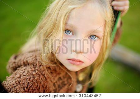 Cute Little Girl Having Fun Outdoors On Sunny Summer Evening. Child Exploring Nature. Summer Activit