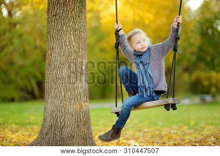 Cute Young Girl Having Fun On A Swing In Sunny Autumn Park. Family Weekend In A City.