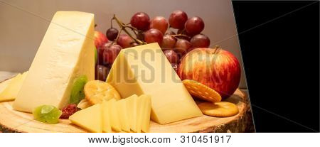 gruyere cheese with variety of fruit and cracker on wooden plate in buffet line, panoramic Large Leaderboard crop size