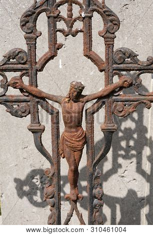Sint Gillis Waas, Belgium, 08 July 2019. Old Rusted Cross With Jesus Christ, The Shadow Falls On A C