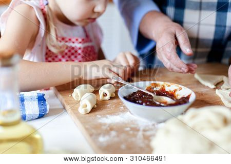 Kid Makes Croissants With Jam. Family Is Cooking Together At Home. Dough And Ingredients Are On Kitc