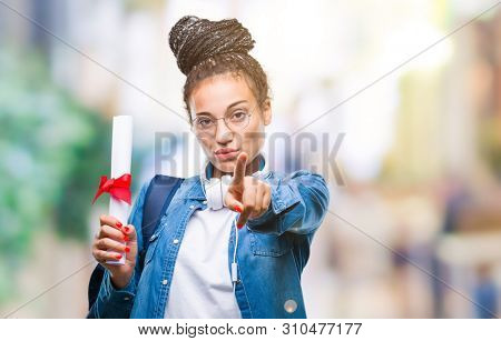 Young braided hair african american student girl holding degree over isolated background pointing with finger to the camera and to you, hand sign, positive and confident gesture from the front