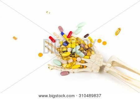 White Bony Skeleton Hand Palm Up Holding A Handful Of Pills