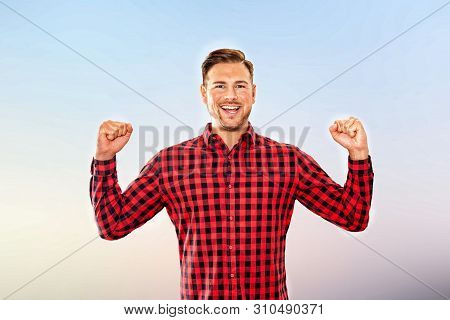 Exultant Man Cheering A Personal Success Laughing And Pumping The Air With Both Fists In An Upper Bo