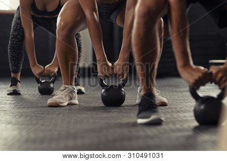 Closeup of young man and fit woman hands lifting kettle bell while squatting at gym. Athlete people doing weight lifting with kettlebell. Group of three young athlete doing fit training.