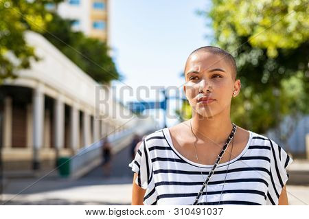 Serious young woman with bald hair lost in deep thoughts. Stylish woman in casual dress looking away thinking. Proud young girl suffering from cancer looking away while standing on road, copy space.