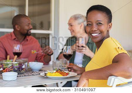 Happy mature african woman looking at camera while having lunch with her friends in background. Portrait of laughing black woman enjoying brunch with smiling senior couple eating and drinking together