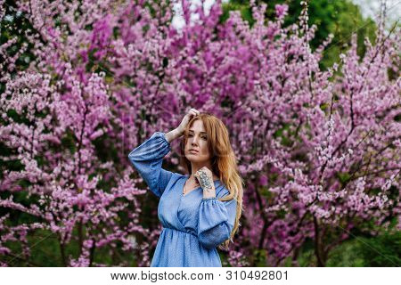 Beautiful Smilling Redhead Woman In Spring Time Blossom Cherrytrees Garden. Perfect Time For A Walk.