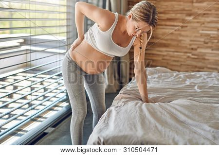 Heavily Pregnant Young Woman Suffering With Back Ache Leaning On Her Bed Clutching Her Lower Back Wi
