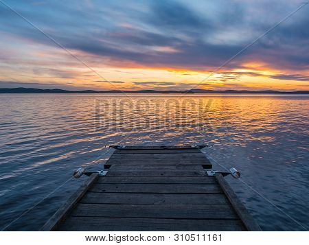 Calm, Serenity, Meditation Concept. Sunset On The Lake, Wooden Bridge In The Foreground, Quiet Water