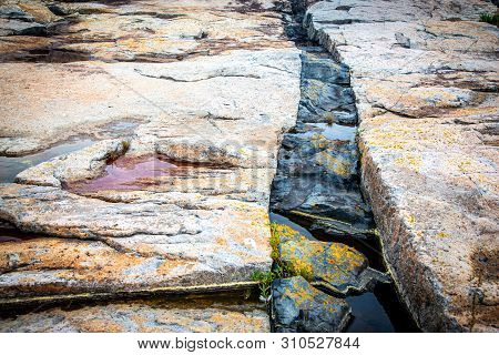 A Crack With Black Intrusive Igneous Basalt Dike Rock And Granite At Schoodic Point In Acadia Nation