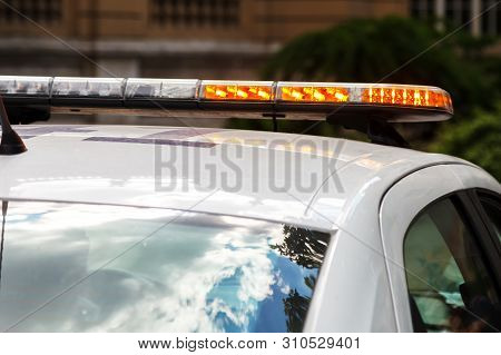 Strobe Light Flashes Orange, Mounted On A Police Car