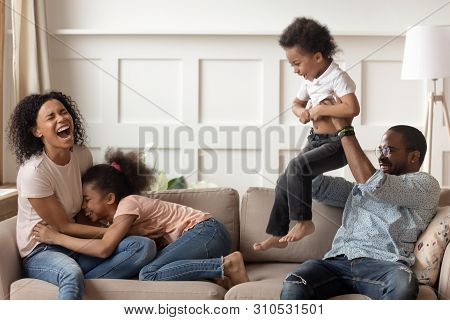 Happy Black Family Having Fun Playing With Children At Home