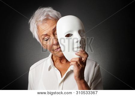 Older Woman With White Hair Hiding Sad Face Behind Mask - Depression Or Personality Concept