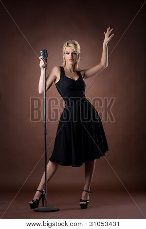 cute woman with microphone on dark background
