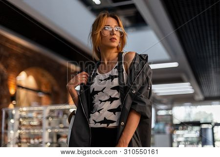 Beautiful Urban Young Hipster Woman In Trendy Glasses In A Trendy T-shirt With A Pattern In A Stylis