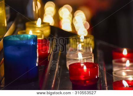 Candles Inside A Church. Sensation Of Religiosity And Tranquility. Bokeh Lights As Space For Text