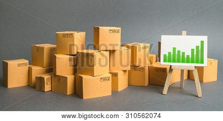 A Large Number Of Cardboard Boxes And Sign With Green Positive Trend Chart. Rate Growth Of Productio