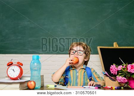 Funny Little Boy In Glasses Sits At Desk In Classroom. Kid In Classroom Have School Lunch. Schoolboy