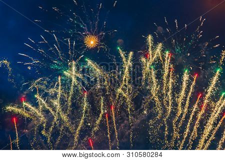 Inexpensive Fireworks Over The City Sky, Red, Blue And White. Bright And Shiny. Selective Focus. For