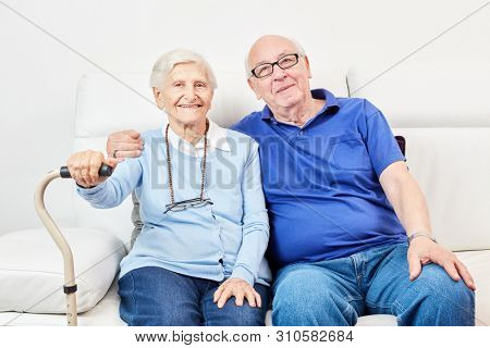 Senior and senior as happy couple sit together on the sofa