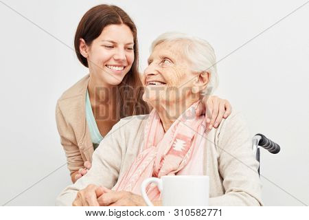Young woman as a granddaughter or care assistant in the care of a senior citizen