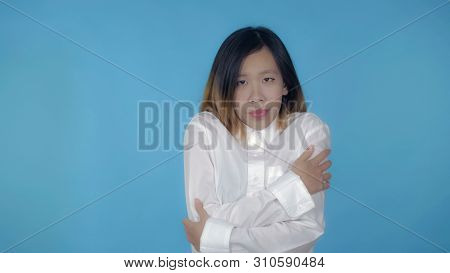 Young Asian Woman Posing Freezes On Blue Background In Studio. Attractive Millennial Girl Wearing Wh